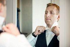 groom-tying-white-bowtie